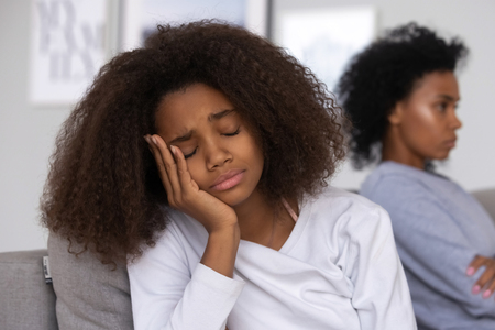 Sad African American teenage daughter sit on couch feel upset after fight with mom, mother and child avoid talking having understanding problems, teen girl disappointed with family relationships