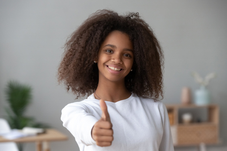 Happy African American teenage girl looking at camera, showing thumbs up pleased with service or online education course, satisfied smiling black pretty teenager gesture recommending something