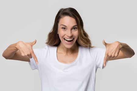 Blogger de niña feliz apuntando hacia abajo con los dedos hacia abajo mostrando suscripción como botón mirando a cámara aislada sobre fondo blanco de estudio en blanco, retrato de producto de publicidad de mujer joven emocionada