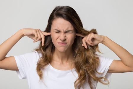 Hartnäckige verärgerte Frau, die Steckerfinger in die Ohren steckt, die nicht auf laute Geräusche hört, die auf weißem, leerem Studiohintergrund isoliert sind, junge wütende Teenager lehnen es ab, Stress zu vermeiden, Ohrenschmerzen-Schmerz-Konzept zu fühlen