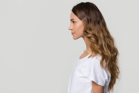 Jonge vrouwelijke duizendjarige vrouw permanent in profiel op witte grijze achtergrond met kopie vrije ruimte voor tekst, zelfverzekerde serieuze meisje dame model geïsoleerd op lege studio muur, zijaanzicht portret