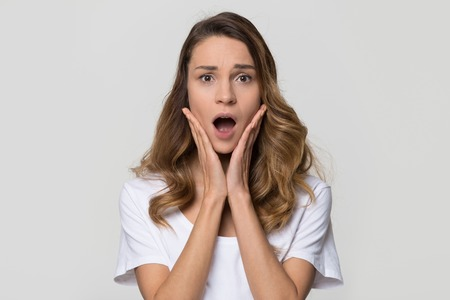 Shocked woman feeling terrified looking at camera on white studio wall, stressed horrified frightened lady in panic with scared face screaming having phobia posing on light blank background, portrait Stock Photo