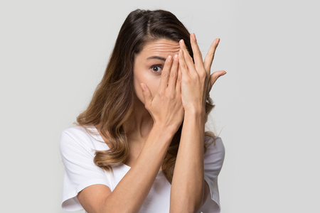 Young curious woman covering face with hands peeping spying eye on white studio wall, funny girl feeling afraid fear shy hiding looking at camera through fingers isolated on light blank background Stock Photo