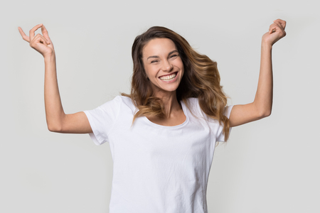 Happy cheerful young woman jumping feeling joy isolated on white studio wall blank background, excited ecstatic girl laughing rejoicing dancing enjoying freedom looking at camera, portrait Stock Photo