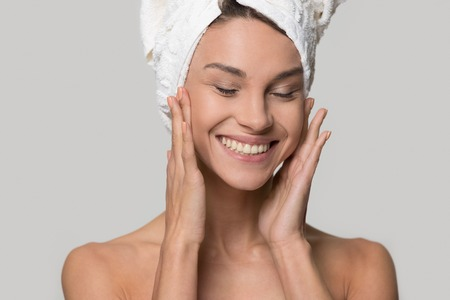 Happy woman girl with towel on head smiling touch healthy clean soft moisturized hydrated skin care after applying cream on young face isolated on white studio background, natural beauty treatment