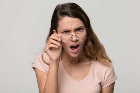 Shocked angry young woman in disbelief lowering glasses looking at camera with indignation isolated on grey blank studio background, confused girl frowning touching eyeglasses feeling flabbergasted Archivio Fotografico