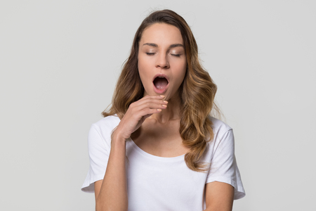 Young tired sleepy disinterested woman yawning isolated on white background, funny lazy bored girl feeling deprived drowsy somnolent on light blank studio wall, lack of sleep gape and boredom concept