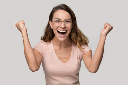 Happy young woman laughing celebrating victory win looking at camera screaming with joy, excited girl winner rejoicing success opportunity triumph isolated on blank grey white studio background