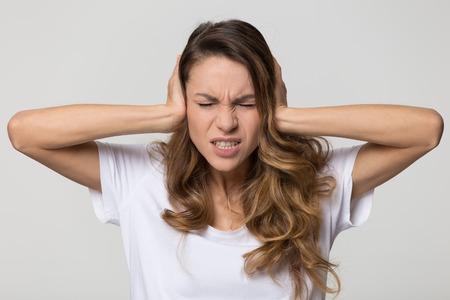 Annoyed stressed woman cover ears feel hurt ear ache pain otitis suffer from loud noise sound headache, irritated stubborn girl deaf hear not listen to noisy music isolated on white studio background Reklamní fotografie - 116390982