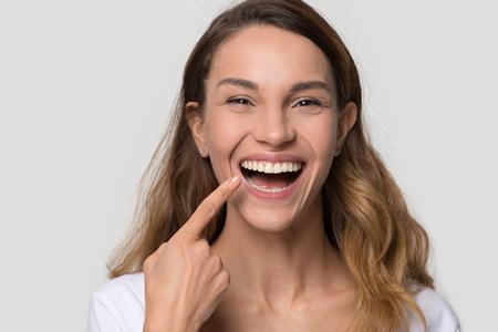 Feliz mujer joven con dientes rectos blancos sonrisa de ortodoncia perfecta abolladura apuntando al diente mirando a cámara aislada sobre fondo blanco de estudio, concepto de servicio de estomatología de salud dental, retrato