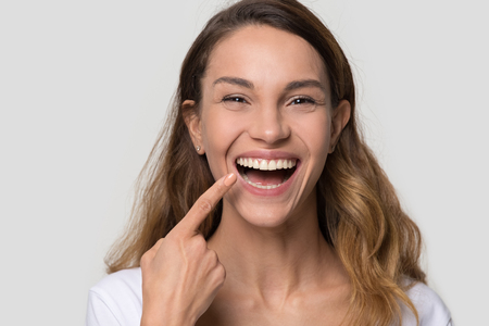 Happy young woman with white straight teeth perfect dent orthodontic smile pointing at tooth looking at camera isolated on studio blank background, dental health stomatology service concept, portrait