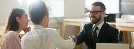Zuversichtlicher Immobilienmakler-Finanzberater im Anzug, der sich mit der Dankbarkeitsgeste des Kunden die Hand schüttelt, gratuliert mit dem Mietkonzept für den Immobilienkauf, dem Banner für das Design der Website-Header