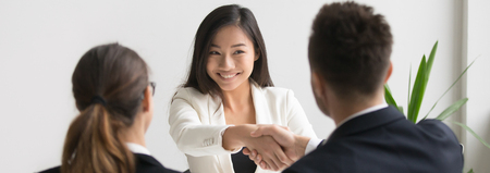 Smiling successful young asian applicant handshake with hr manager feels happy getting hired, boss congratulating employee new job employment concept. Horizontal photo banner for website header design 写真素材 - 116422035