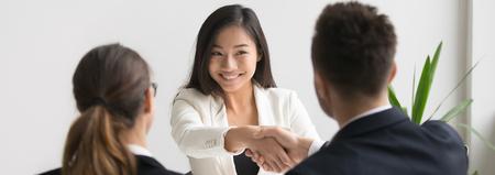 Une poignée de main souriante et réussie d'un jeune candidat asiatique avec le responsable des ressources humaines se sent heureux d'être embauché, le patron félicite le nouveau concept d'emploi de l'employé. Bannière photo horizontale pour la conception d'en-tête de site Web Banque d'images