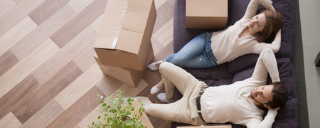 Horizontal above concept photo married couple at moving day rest relax on couch cardboard boxes on floor feels satisfied breathing fresh air, banner for website header design with copy space for text Imagens