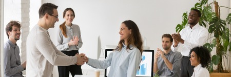 Boss welcoming new employee hired intern female, mixed race woman feel happy promoted receive appreciation for good work result from company head colleagues applauding banner for website header design Stock Photo