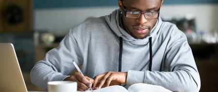 Closeup smart millennial african student wear glasses hold pen noting writing down information study use book preparing for university or college test exam, horizontal photo banner for website header Stockfoto