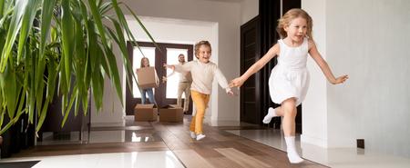 Foto orizzontale bambini felici che corrono nella nuova casa, genitori con scatole di cartone sullo sfondo. Mutuo di prestito, banner di concetto di trasferimento in movimento per il design dell'intestazione del sito Web con spazio di copia per il testo