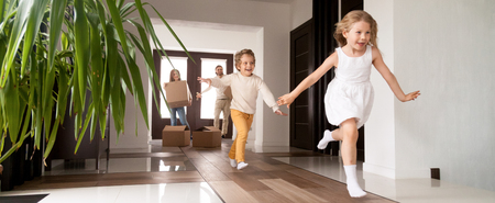 Horizontal photo happy little kids running into new home, parents with cardboard boxes on background. Loan mortgage, moving relocating concept banner for website header design with copy space for text Banque d'images