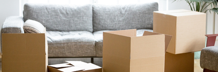 Horizontal photo heap of cardboard boxes with personal belongings in living room at moving relocation day no people, delivery service concept, banner for website header design with copy space for text Stock Photo