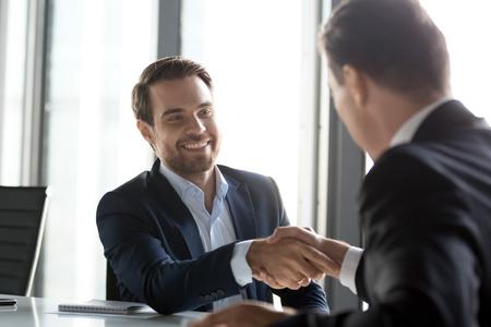 Fröhliche Geschäftsleute in Anzügen, die nach erfolgreichen Verhandlungen beim Treffen die Hände schütteln, männliche Partner, die Geschäfte machen oder einen guten Eindruck machen, sich für vielversprechende Loyalität bedanken, Dankbarkeits-Händedruck respektieren