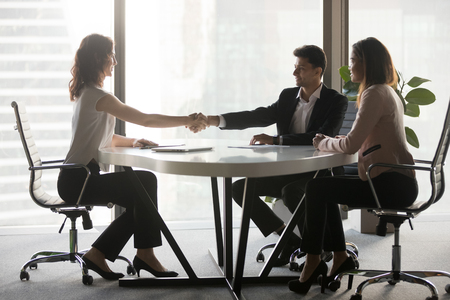 Happy diverse business partners handshaking at office meeting, arab hr congratulates job seeker shake hands hiring concept, respect, make deal first impression, thank for cooperation partnership