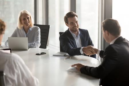 Gelukkige zakenpartners die handen schudden om respect te betuigen, zakelijke deal voor bankinvesteringen sluiten, verwelkomen op kantoorgroepsvergadering, handdruk van lachende zakenlieden als samenwerkingsconcept Stockfoto