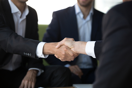 Close up view of two businessmen in suits shake hands at group meeting, business partners handshaking after successful negotiation closing good deal, respect and loyalty, union, reliability concept