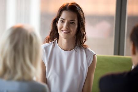 Fiducioso felice richiedente richiedente millenario che sorride guardando hr durante il colloquio di lavoro, giovane donna d'affari sorridente che partecipa a negoziati di riunioni di lavoro, reclutamento, concetto di prima impressione