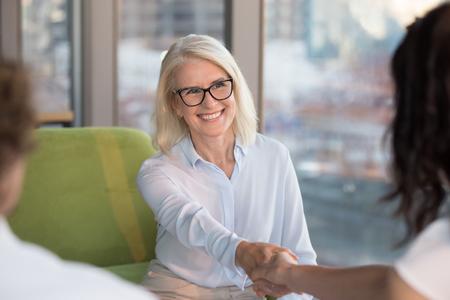 Lächelnd selbstbewusste alte reife Frau Arbeitssuchende Bewerberin Handshaking hr macht einen guten ersten Eindruck beim Vorstellungsgespräch, glückliche zufriedene Geschäftsfrau mittleren Alters, die die Hand schüttelt
