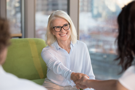 Smiling confident old mature woman job seeker applicant handshaking hr making good first impression at interview meeting, happy satisfied middle aged businesswoman shaking hand getting hired concept Stock Photo