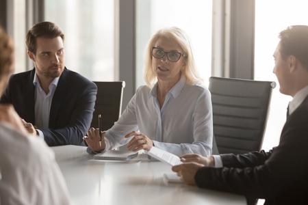 Ernsthafte Geschäftsfrau mittleren Alters spricht bei der Vorstandssitzung der Gruppe, selbstbewusste reife alte weibliche Führerin, die über die Arbeit spricht, bietet Lösungsverhandlungen mit Partnern beim Unternehmensbriefing