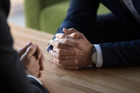Clasped male hands of two businessmen negotiate at table, hr recruiter making hiring decision at difficult job interview, opponents dialogue debate, business confrontation challenge concept, close up