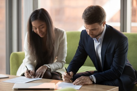 Asian businesswoman and caucasian businessman sign contracts documents at meeting, diverse male female business partners client and service provider put signature on legal papers making agreement