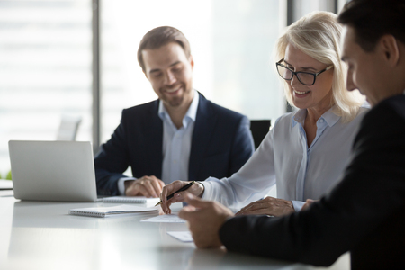 Smiling middle aged older businesswoman signing paper contract at group meeting, happy mature senior woman client puts signature on business document fills form making agreement deal, getting hired Reklamní fotografie