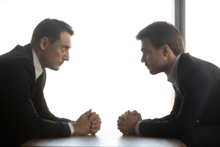 Two confident businessmen with clasped hands look at each other sitting opposite as rivalry confrontation concept, business opponents competitors politicians debate, difficult negotiations, side view 免版税图像 - 116456973
