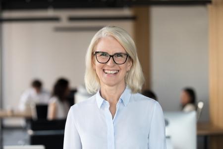 Fröhliche ältere Geschäftsfrau mit Brille, die in die Kamera schaut, glücklicher älterer Teamleiter, CEO, Lehrerin im Alter oder Mentorin, die im Büro lächelt Standard-Bild