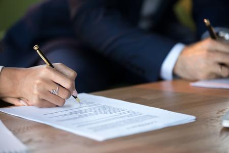 Close-up van vrouw en man die document ondertekenen dat contractconcept sluit en huwelijkse voorwaarden maakt die advocatenkantoor bezoeken, vrouwelijke en mannelijke partners of echtgenoten die handtekening schrijven op decreetpapier