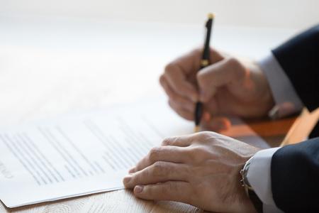 Vista cercana de la mano masculina que firma el concepto de contrato financiero comercial, el empresario puso la firma escrita en el formulario de documento de llenado de papel legal comprar seguro, servicios bancarios, registro autorizado