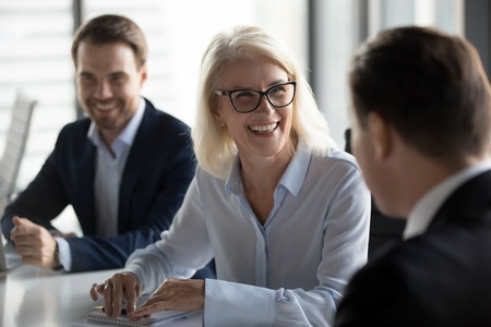 Friendly middle aged female leader laughing at group business meeting, happy old businesswoman enjoying fun conversation with partner, smiling mature business coach executive talking to colleague Stockfoto