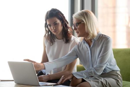 Gerente ejecutivo de mediana edad serio que explica el trabajo en línea de un colega apuntando a una computadora portátil, una aseguradora asesora financiera mayor madura o un trabajador bancario que ofrece al cliente, servicios de asesoramiento