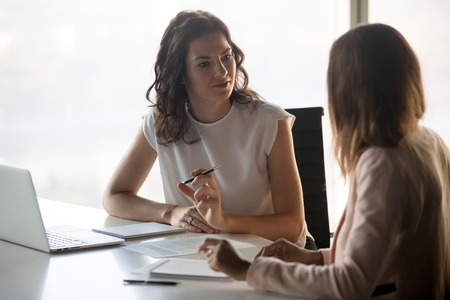 Two diverse serious businesswomen discussing business project working together in office, serious female advisor and client talking at meeting, focused executive colleagues brainstorm sharing ideas Stock Photo