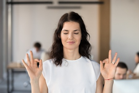 Young business woman employee meditating in office with eyes closed for no stress free relief, hoping for success, doing yoga exercise for relaxation or concentration at work, autosuggestion concept