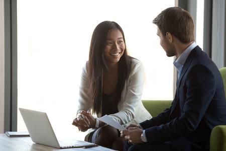 Amable agradable gerente asiático asegurador hr sonriendo hablando con el candidato en una entrevista de trabajo o reunión de negocios prometiendo beneficios contractuales, feliz asesor financiero diverso y cliente conversando