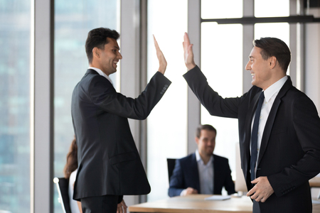 Happy excited arabic and caucasian executive in suits giving high five in office motivated by business success celebrating victory, achievement win or successful deal, support, good result concept 写真素材