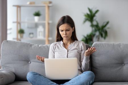 Mujer joven confundida que mira en la computadora portátil en casa sintiéndose desconcertada por la falta de conexión, leyendo noticias en línea en Internet, chica adolescente molesta enojada con un problema de computadora atascado, correo electrónico no deseado de estafa, error del sistema