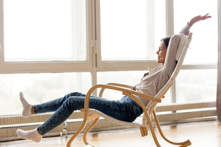 Carefree young woman relaxing on comfortable wooden rocking chair at home, happy millennial girl  resting in living room near window feeling stress free enjoying healthy quiet day chilling on leisure Archivio Fotografico