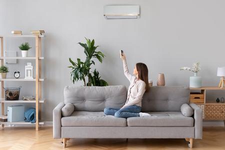 Junge glückliche Frau schaltet die Klimaanlage ein, die auf der Couch in einem bequemen gemütlichen Zuhause sitzt, die Dame entspannt sich auf dem Sofa im Wohnzimmer und hält die Fernbedienung der Klimaanlage, um die Komforttemperatur des Kühlsystems einzustellen