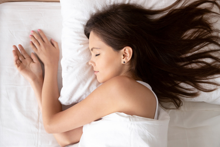 Young calm woman sleeping well in cozy comfortable bed lying on soft pillow orthopedic mattress, serene millennial girl resting enough in good healthy sleep nap on white cotton fresh sheets, top view 免版税图像