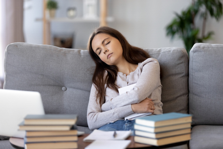 Tired teen girl falling asleep exhausted after long hours of learning exam test preparations, deprived college student sleeping sitting on couch having nap dozing on sofa holding book bored of study Stock fotó